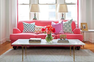 Pinkes Sofa mit geometrisch gemusterten Kissen