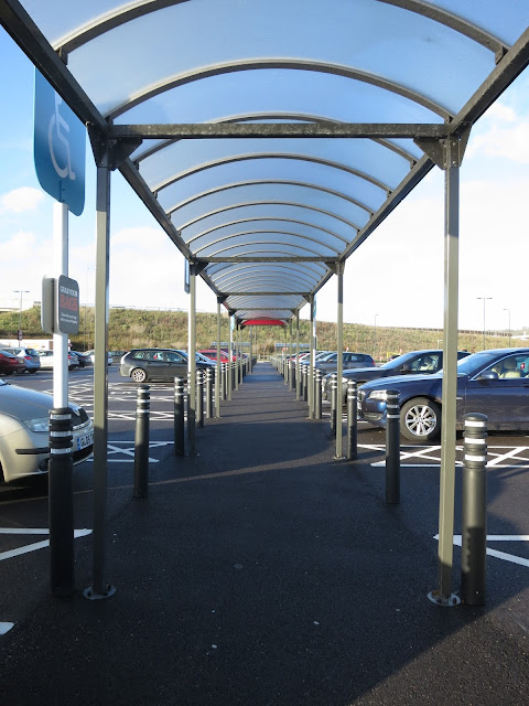 Covered walk in supermarket car park with small tree and grassy bank at end.