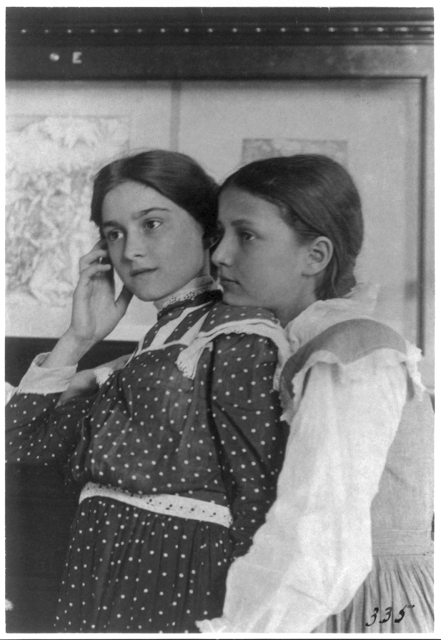 Two girls from a Washington, D.C., school on a class visit to the Library of Congress, looking at an exhibit of relief or wood engravings, one with her chin on shoulder of the other, 1899.