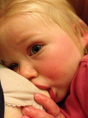 Toddler breastfeeding with visible blister from Hand, Foot and mouth disease on her hand