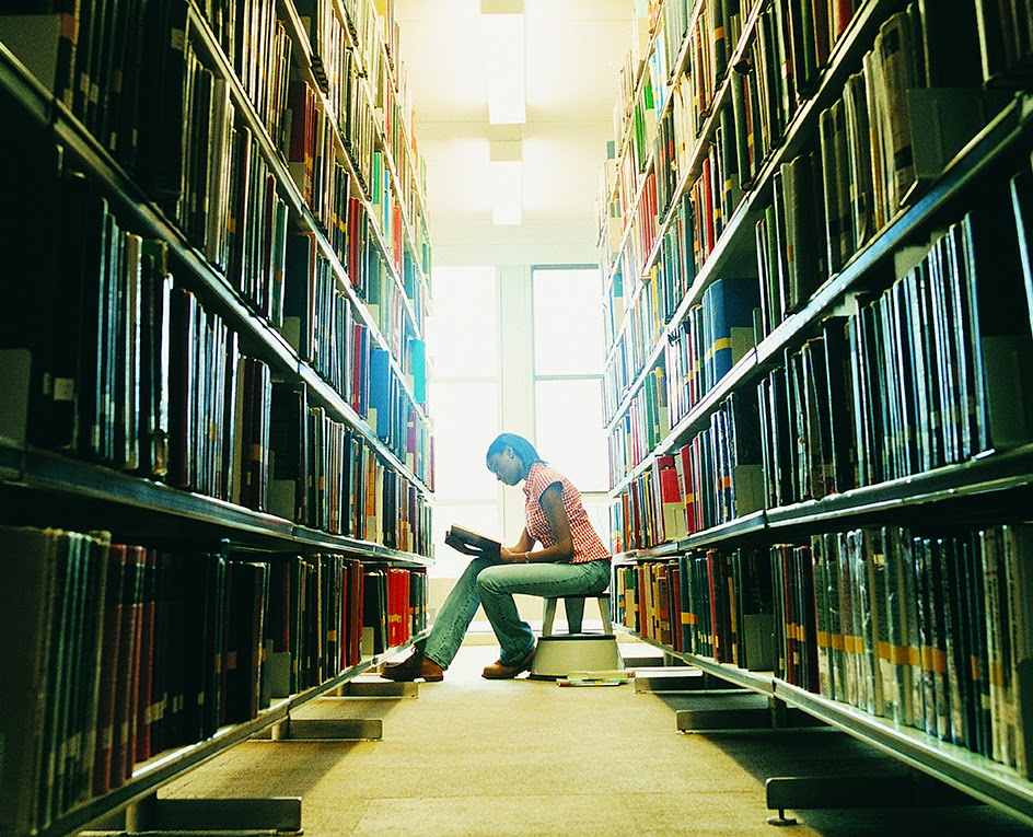 image of a woman in a library reading among stacks of books.