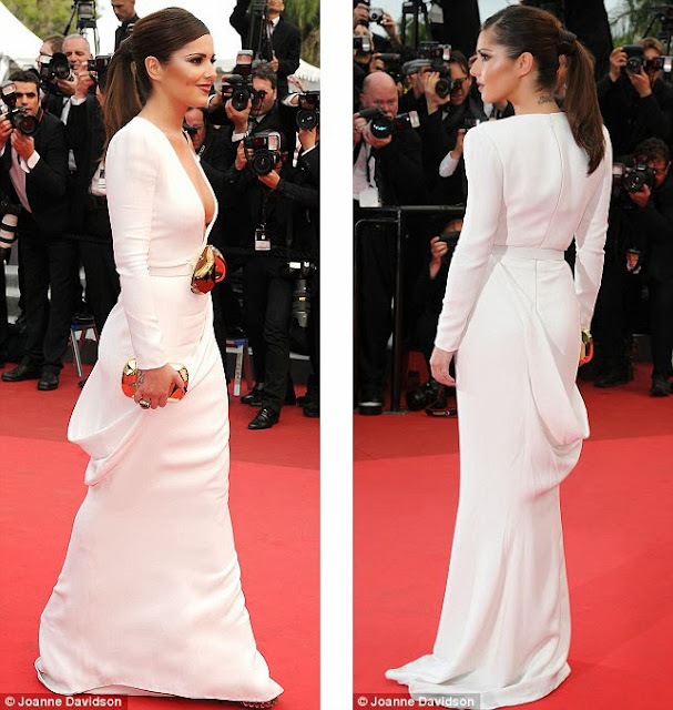 Poised: Cheryl teamed the white dress with an unusual gold belt and matching clutch box bag