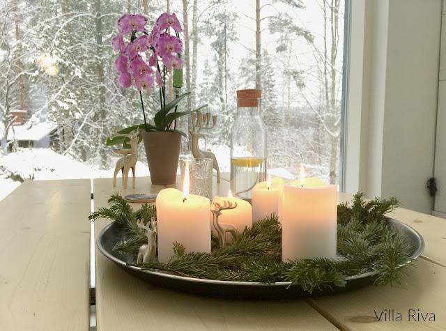 Ruokapöytä, isot ikkunat, kynttilä, kynttiläasetelma
