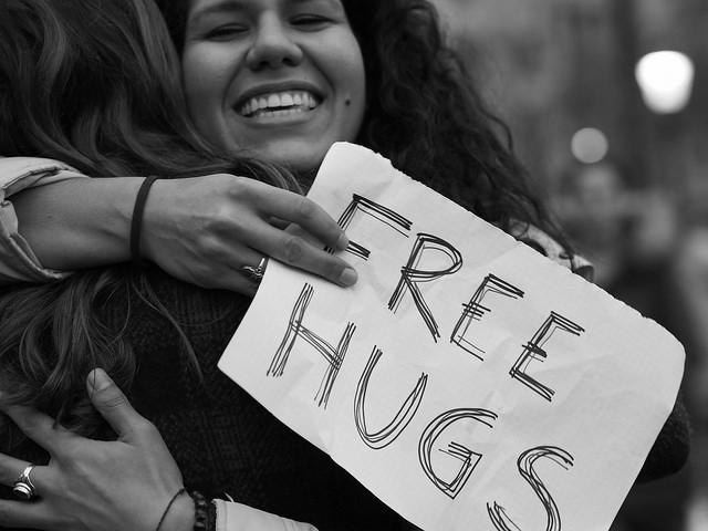 Two women hugging, one with a 'Free Hugs' sign