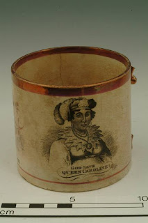 mug with a metallic rim, missing handle, and black and white portrait of the queen with 'God save Queen Caroline' written below it