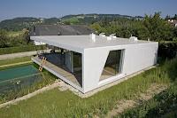 modelo de casa moderna blanca con grandes ventanales un piso vista trasera