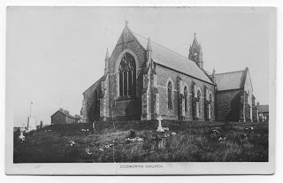 A greyscale photo from an old postcard of St John's Cudworth from the South West, a good view of the West window and the bell tower at the far end of the Nave roof. The war memorial is to the left