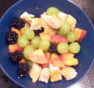 finger food bowl of grilled boneless chicken breast cut into squares with cut up peaches, grapes, and blackberries