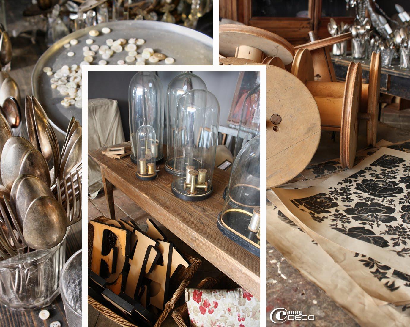 Vieux couverts en argent rangés dans des pots à confiture, bobines de fil industrielles en bois et vieilles planches sérigraphiées et collection de globes Napoléon III