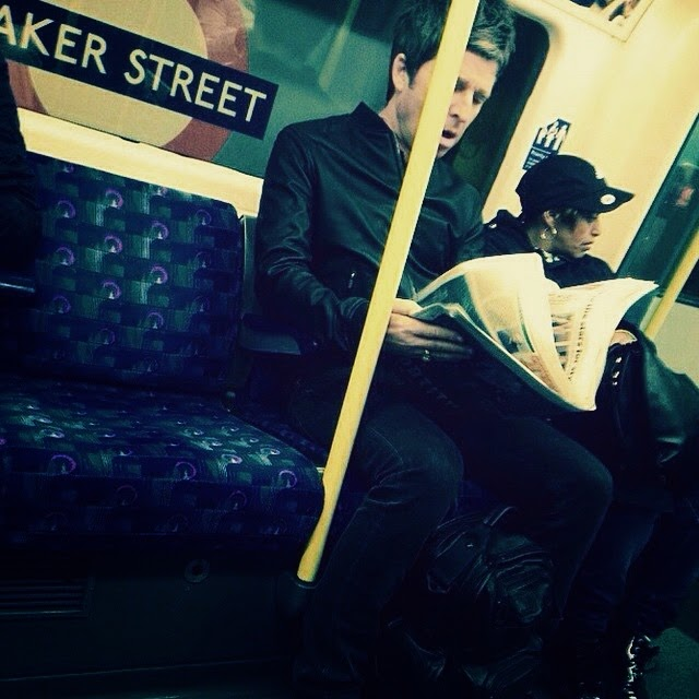 noel gallagher reading the paper on the bus