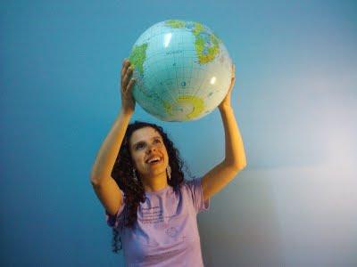 Sara sorri para um globo terrestre erguido por suas mãos. Ela veste uma camiseta lilás com o nome do blog, subtítulo e logo