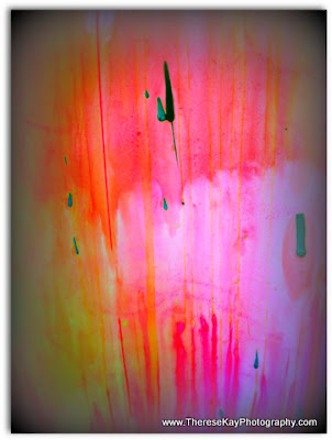 abstract photograph of paint splatters - pink, yellow, orange, green