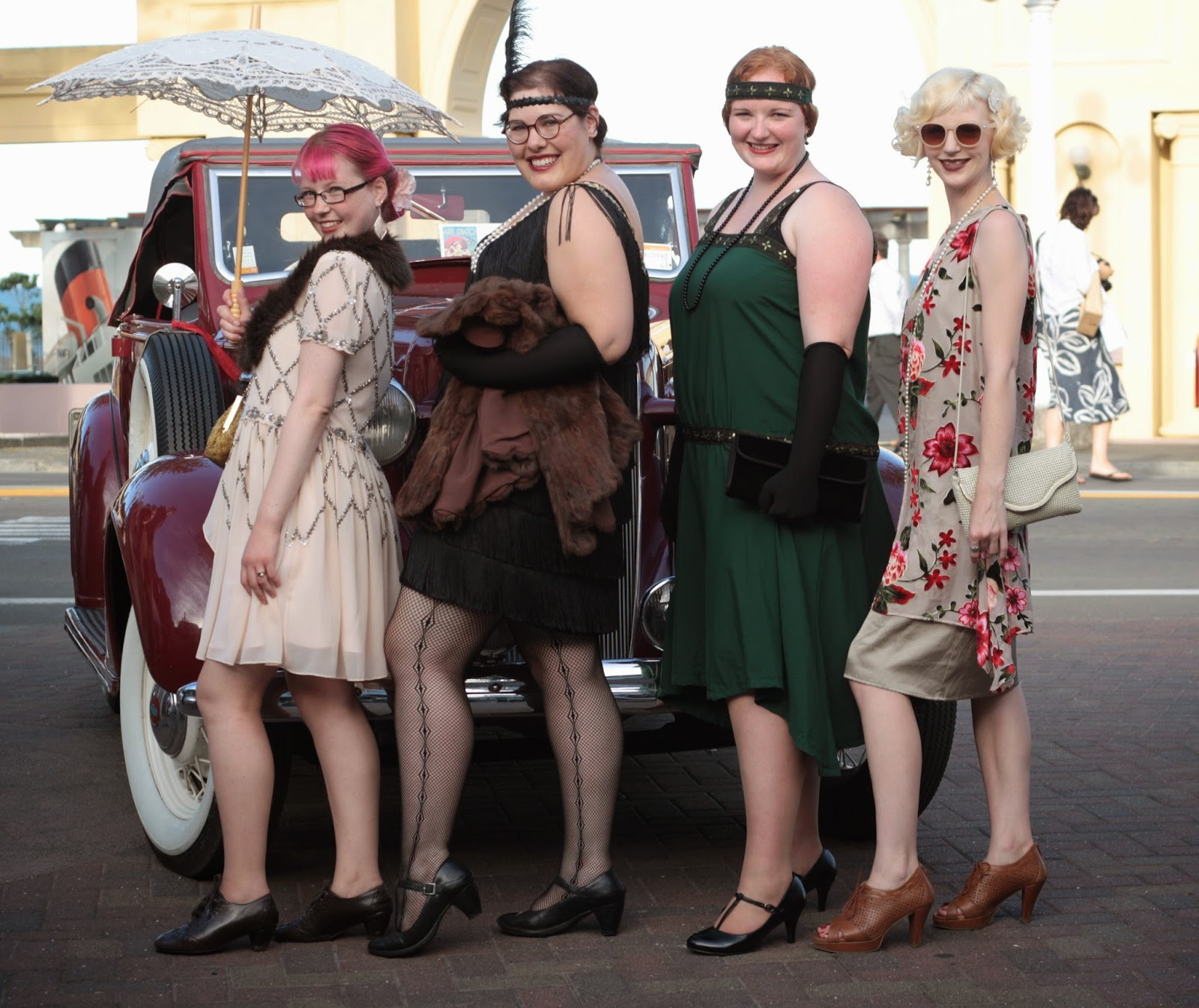 Four girls in art deco flapper costumes pose in front of a vintage car.