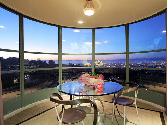 Photo of round glassy table with chairs by the window with Los Angeles view