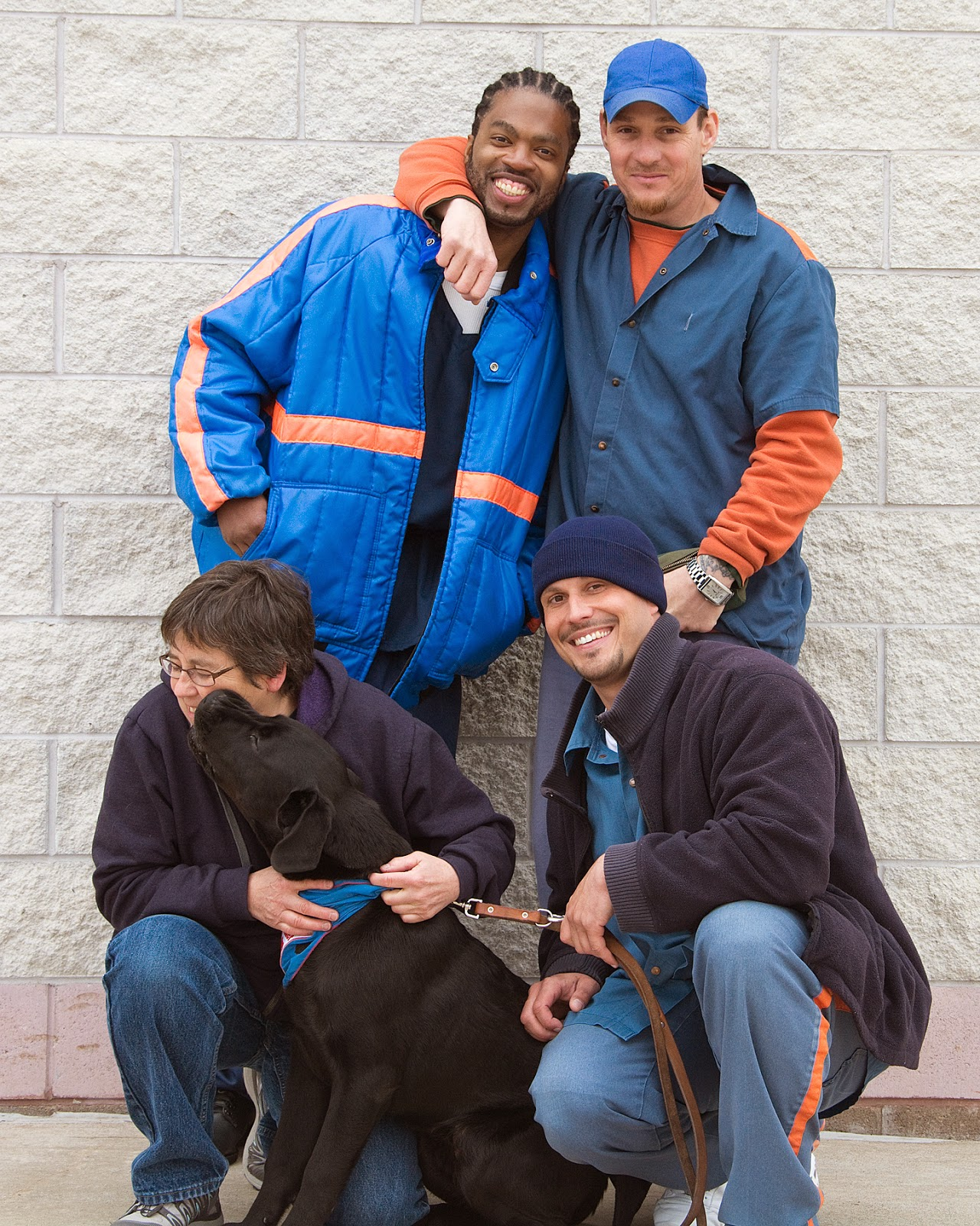 The same group in this picture, but now the man standing on the right in back has his right arm around the african american's neck. The black lab puppy is licking the face of the woman, who is turning her head to the left. The three men are looking at the camera wtih big smiles.