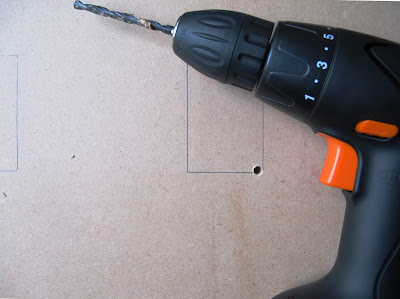 Electric drill on a piece of MDF board, with two rectangles drawn on it, one of which has a hole drilled in the corner of it.