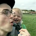 Garotinho dando risada com seu pai assoprando um dente-de-leão