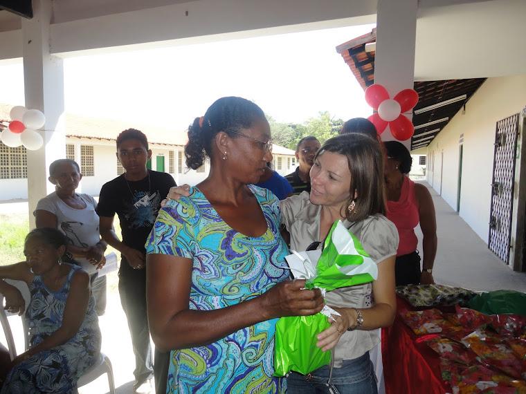 Professora Silvia entregando um pequena lembrança para uma mãe.