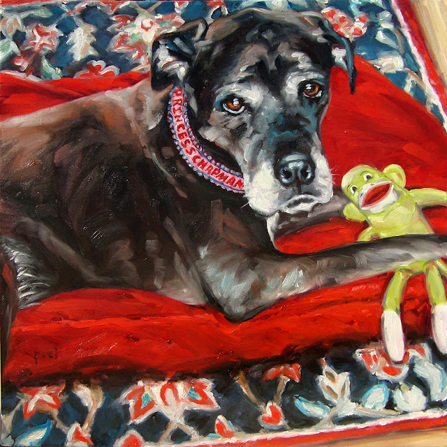 Black Lab and Bulldog mix, lying on her red blanket with monkey toy. Princess is looking up at us.