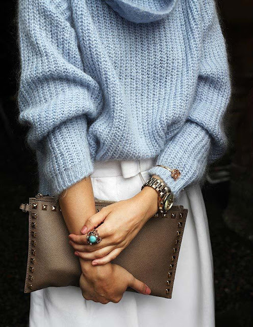 Chunky light blue sweater with a white skirt and tan clutch