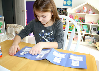 "After creating a quick accordion-fold construction paper booklet of various types of snowflakes for ""Frosty Figures,"" Tessa decorated the front cover with snowflakes drawn with glitter glue."