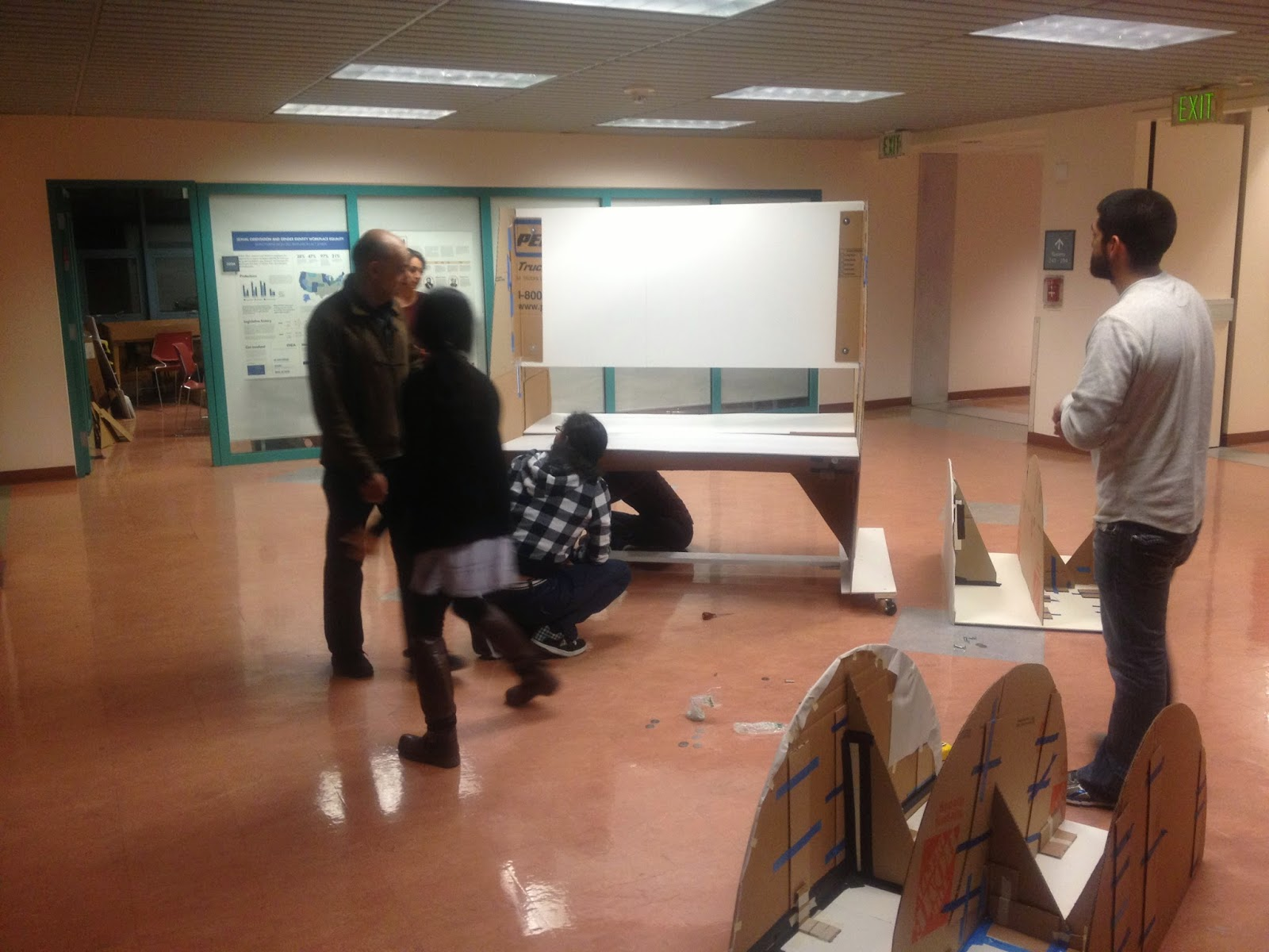 A group of students are assembling a cardboard exhibit display model. The instructor walks over to inspect on the progress.
