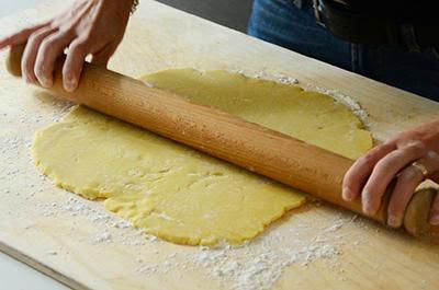 Crostata di mele: stendere il panetto di pasta frolla con un mattarello
