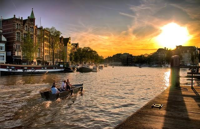 ocaso en amsterdam, ocaso debajo del nivel del mar en holanda, bote en la ciudad de amsterdam, rio y bote en la ciudad en holanda.