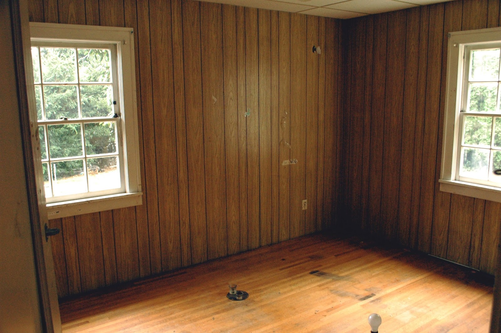 faux wood paneling thrashed wood floor windows nailed shut dropped ceiling with curious water stain - Wood Paneling With Wood Floor