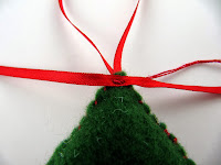Sewing a ribbon to a felt Christmas tree decoration