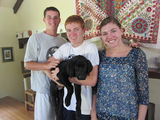 Connor, Austin and Allie, Austin's sister stand in front of the fireplace.  Austin is holding Coach.
