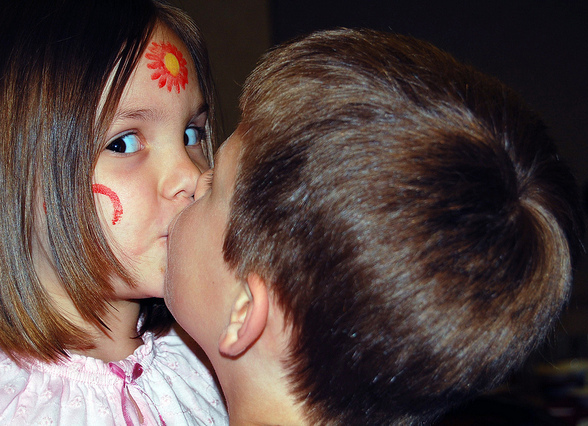 A young girl looks knowingly at the camera as she kisses a boy