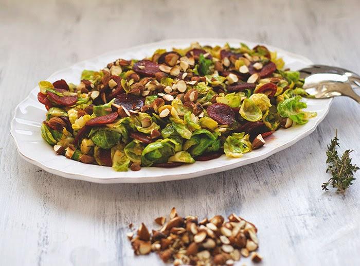 Salat aus Rosenkohl, Chorizo und gerösteten Mandeln, auf einer Servierplatte angerichtet