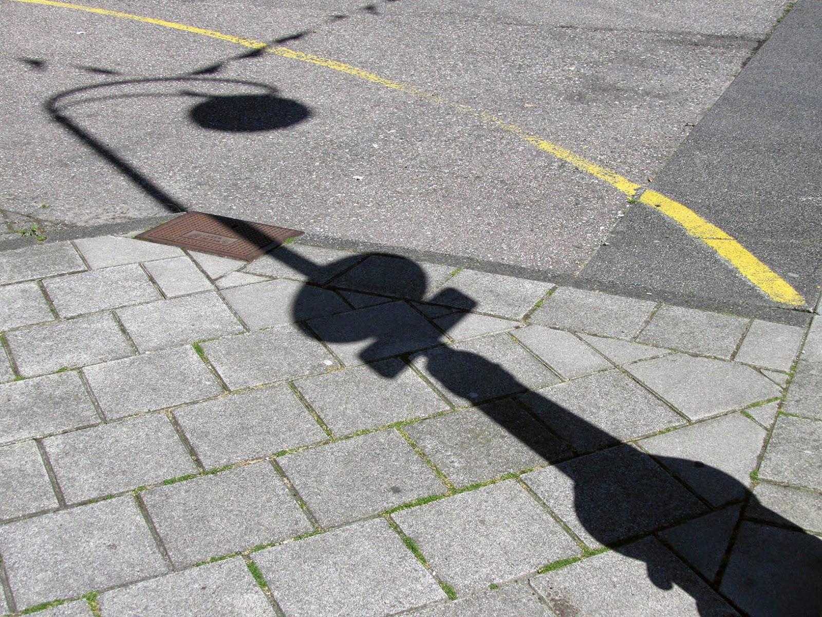 shadow of a lamppost on sidewalk