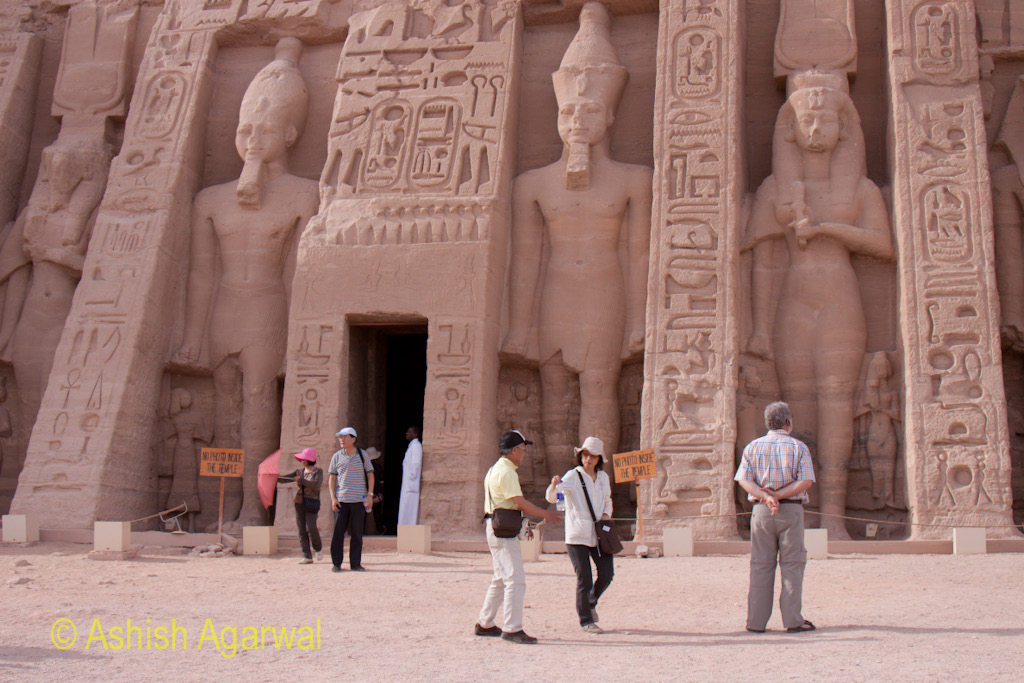 A few tourists outside the smaller temple of the Abu Simbel temple complex