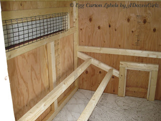 Droppings boards are installed underneath the roosts in the chicken coop.