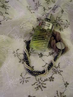 Lana islandese tinta naturalmente grigio, perle di fiume su lino ricamato e Eau de Rochas