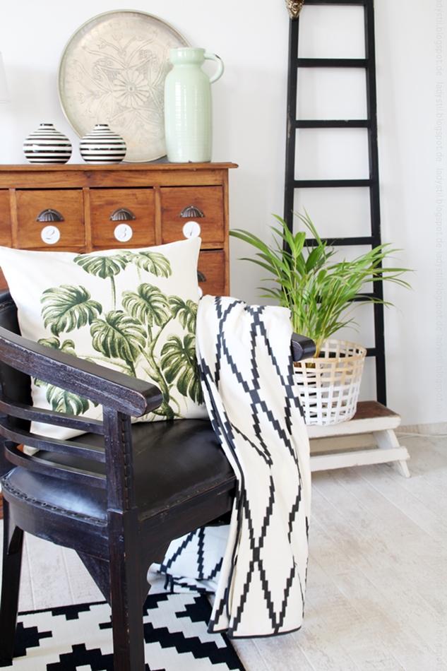 antiker Stuhl mit Kissen auf dem eine Monstera-pflanze abgebildet ist vor einer Kommode mit schwarzweißen Vasen und silbernem Tablett neben einer schwarzen Leiter