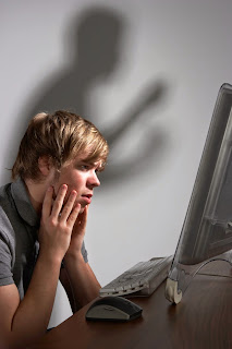 Teenaged boy sits over his computer, while a shadow with fists hovers over him.
