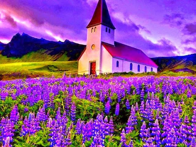 Imagen de un hermoso paisaje con un cielo en tonos violetas, montañas de fondo y mas cerca una iglesia frente a un campo de lavandas en flor