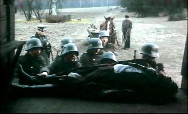 """Anielin. Kadr z filmu """"Hubal"""" w reżyserii Bohdana Poręby (1973). Rolę Hubala w filmie odtwarzał Ryszard Filipski. O świcie 30 kwietnia 1940 r. ciało Hubala przewieziono furmanką w okolice kapliczki i złożono na platformie ciężarówki. W głębi """"nasza"""" kapliczka."""
