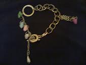 pulseira dourada c elos e pingentes coloridos