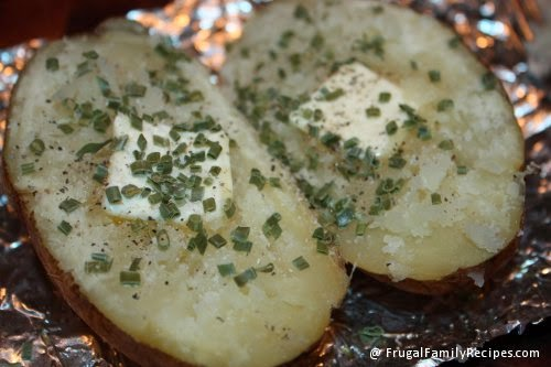 Potatoes cooked in crock pot, with a pat of butter and dried chives.