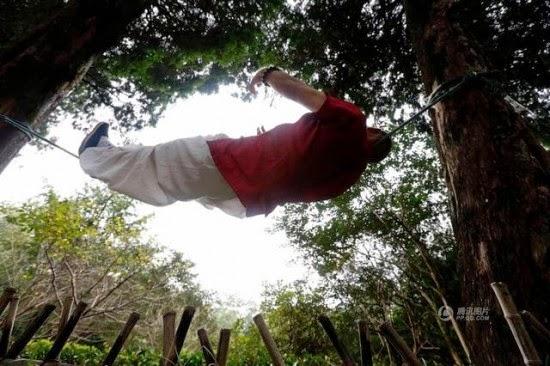رجل الحبل يستلقي على الحبل بين شجرتين