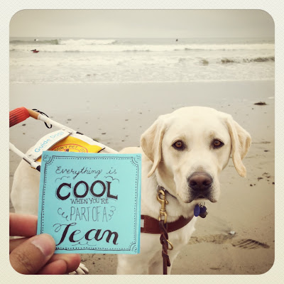 "JR holds up a post it with his unique typography that says ""Everything is cool when you're part of a team"" with his guide dog Griff and the ocean in the background."
