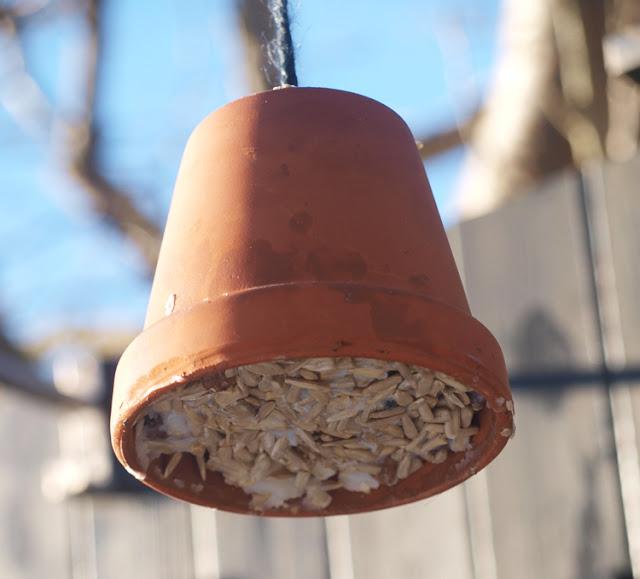 Lerpotte med fuglemad i haven