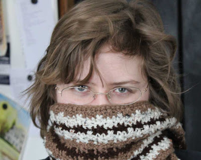 woman with face covered by crocheted scarf