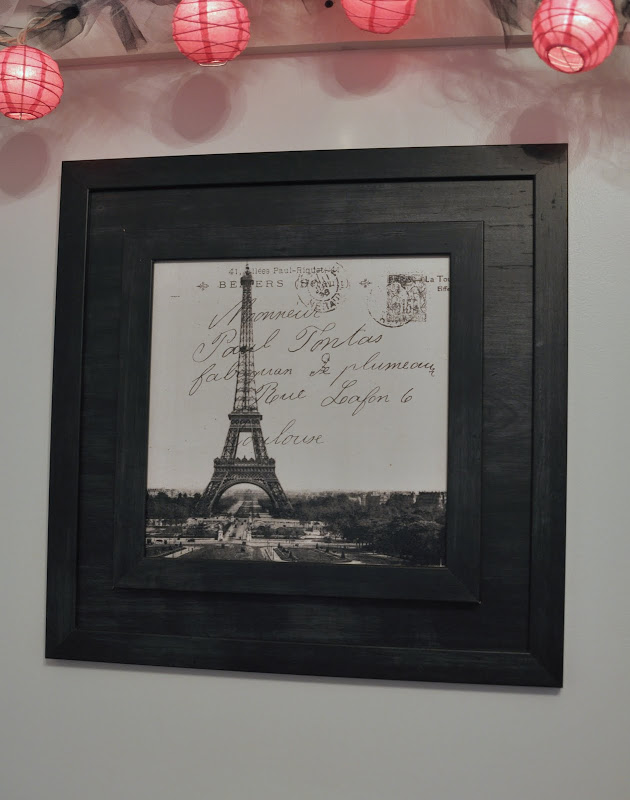 An up close look at the Paris picture above her bed. title=