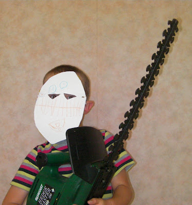 boy with homemade mask and hedge trimmer