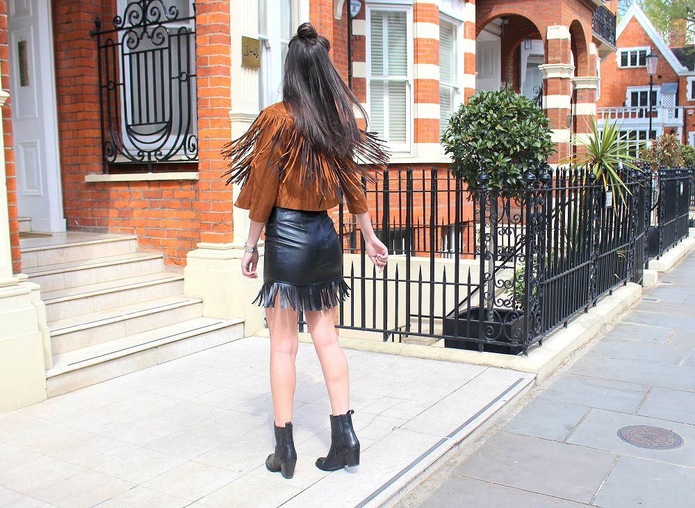peexo-fashion-blogger-wearing-fringe-jacket-and-leather-skirt-and-boots-and-white-tshirt-and-round-sunglasses-in-spring=70s-inspired